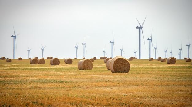風力タービンと夏の曇りの日にフィールドで干し草の俵。エネルギー生産、クリーンで再生可能なエネルギー。