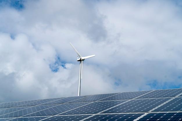 Ветряные турбины и солнечные батареи на фоне яркого неба