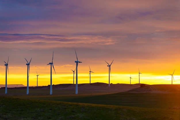 Wind turbines in field against sunset sky, spain
