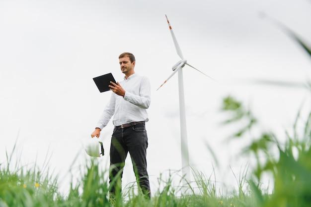 Ветряные турбины, вырабатывающие электроэнергию. концепция энергосбережения и рабочий штатный инженер удерживают планшет
