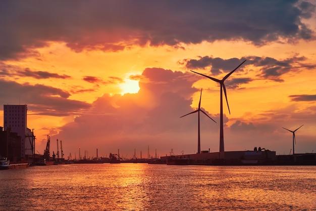 日没時のアントワープ港の風力タービン