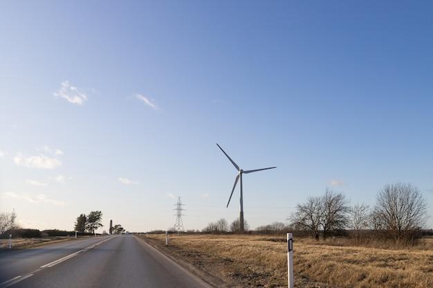 Ветротурбины в ветропарке против облачного неба. генератор энергии ветра ветротурбина над небом. производство электроэнергии из возобновляемых источников. экоэнергия, ветряные турбины.