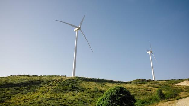 푸른 하늘 배경 위에 전기를 생성하는 언덕에 풍력 터빈. 깨끗하고 생태학적인 에너지 생산 개념입니다.