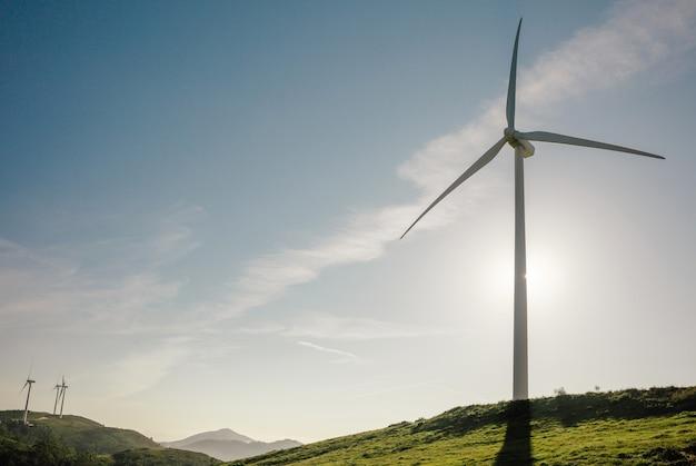 푸른 하늘 위에 전기를 생성하는 언덕에 풍력 터빈. 깨끗하고 생태학적인 에너지 생산 개념입니다.