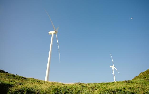 푸른 하늘에 전기를 생성하는 언덕에 풍력 터빈. 깨끗하고 생태학적인 에너지 생산 개념입니다.