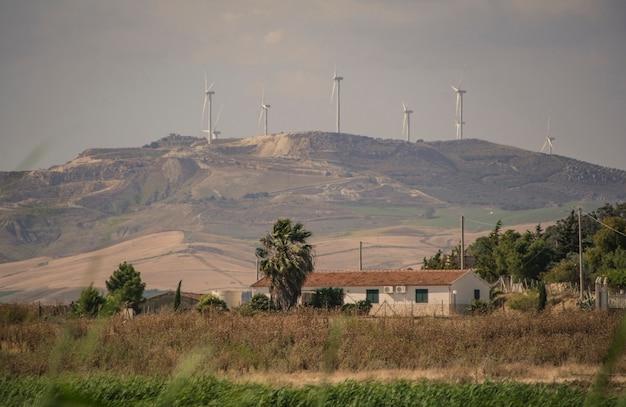 イタリアのシチリア島の丘の上に設置された、電気エネルギーを生産するための風力タービン...