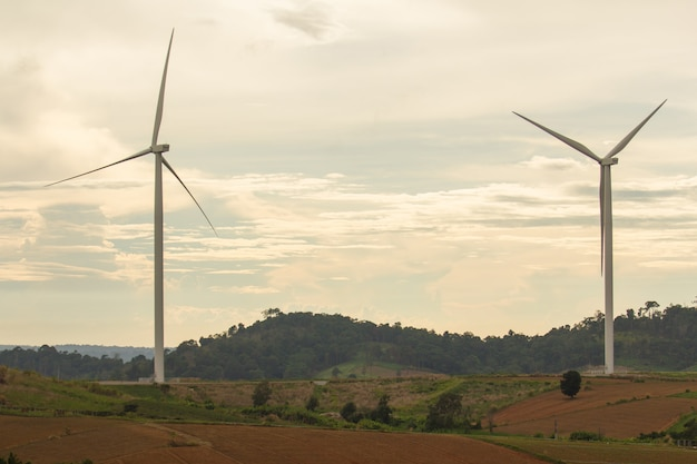 Wind turbines power on mountain with sunset sky