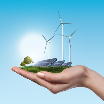 Wind turbines and solar panels on meadow with tree holds in woman's hand against blue sky and clouds