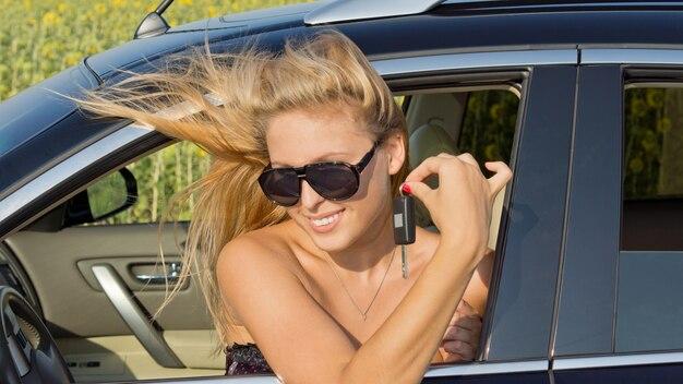 바람에 날린 여자는 그녀의 손가락 사이에 키를 들고 창 밖으로 그녀의 머리와 함께 차에 앉아
