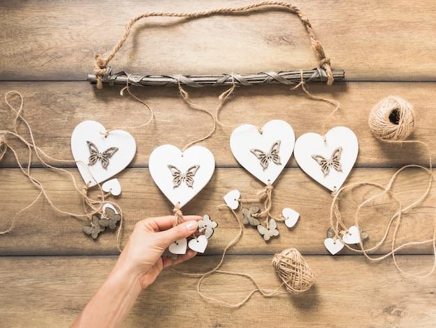 スプールで木製の厚板に心臓windchimesを保持する人