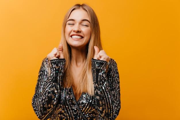 Donna allegra allegra che gode del servizio di ritratti sull'arancia graziosa donna bionda che ride con gli occhi chiusi.