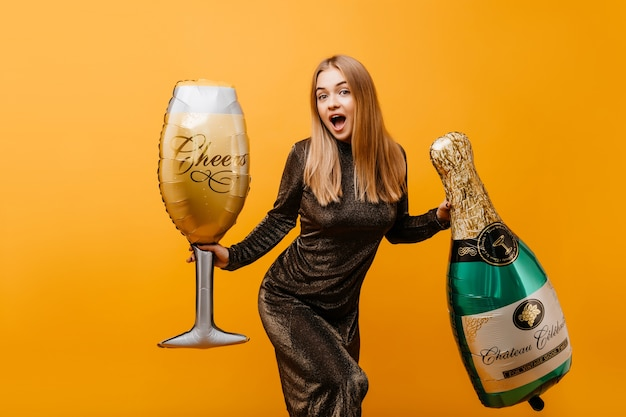 생일 파티에서 놀란 이모티콘을 표현하는 스트레이트 헤어 스타일로 바람이 부는 여자. 샴페인과 와인 글라스의 병으로 아름 다운 우아한 여자의 실내 초상화.