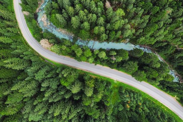 緑の松林を流れる川のある曲がりくねったアスファルトマウンテンロード道路