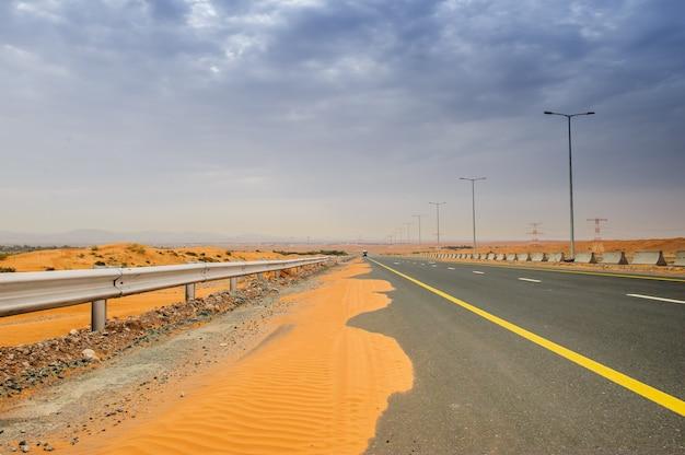 アラブ首長国連邦、リワオアシスの砂丘を通る曲がりくねった黒いアスファルト道路