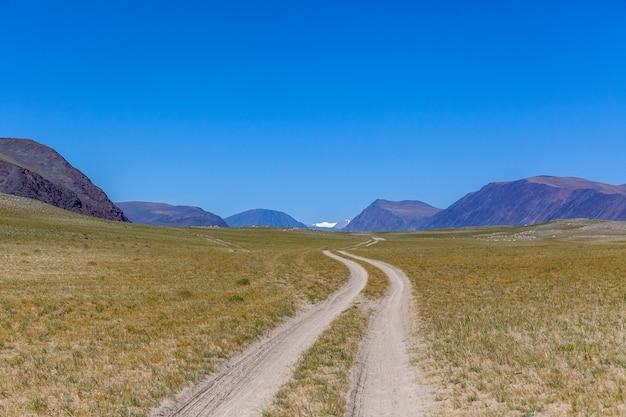 中央モンゴルの草原の緑豊かななだらかな丘を通る曲がりくねった未舗装の道路。モンゴルアルタイ