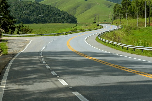 Winding highway with green fields on the horizon