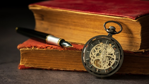 Winding pocket watch placed beside the old book and the pen on the book in darkness and morning light.