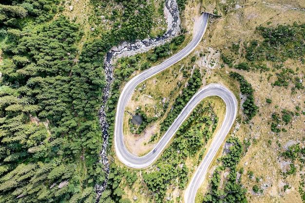 山の中の曲がりくねった道。近くの森と川。 trasnylvania、ルーマニア、ヨーロッパのトランスファガラシャン道路。