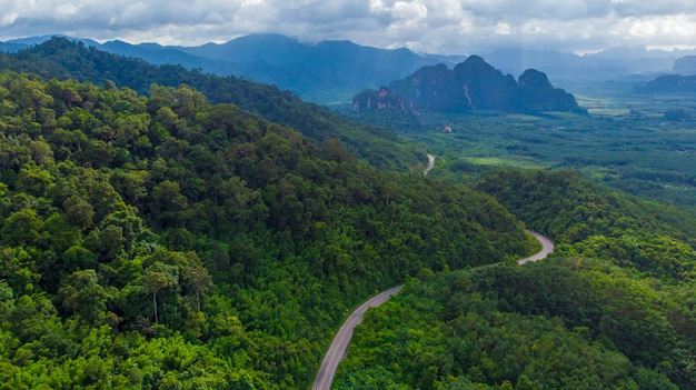 Winding road in mountain valley at sunset. aerial view of asphalt road in thailand. top view of roadway, mountains, green forest, blue sky and sunlight