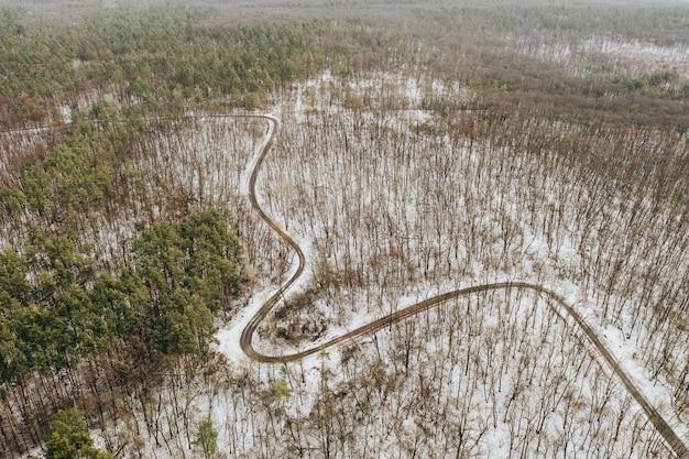 Извилистая дорога через зимний заснеженный лес без листьев. фото дрона.