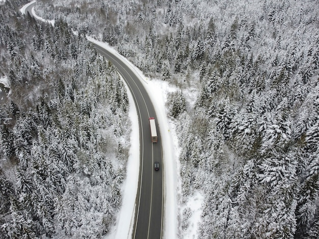 Извилистая дорога через лес зимой. асфальт через перевал на вершину горы в румынии