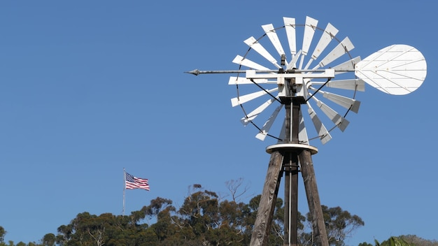 Windmill, bladed rotor and usa flag against blue sky. water pump wind turbine, power generator.
