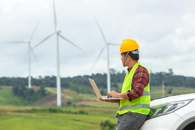 Инженер ветряной мельницы осматривает и проверяет ход работ ветротурбины на строительной площадке используя автомобиль в качестве транспортного средства.