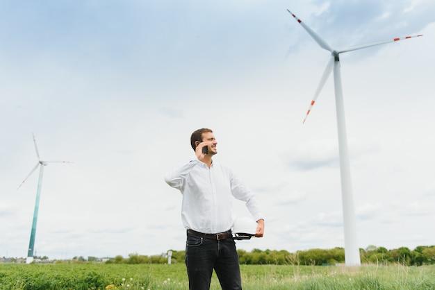 Инженер ветряной мельницы разговаривает по телефону на ветряной мельнице. мужчина в шлеме наблюдает за работой электрических ветряных мельниц. Premium Фотографии
