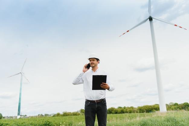 風車の電話で話している風車エンジニア。ヘルメットをかぶった男が電気風車の運転を監督している。