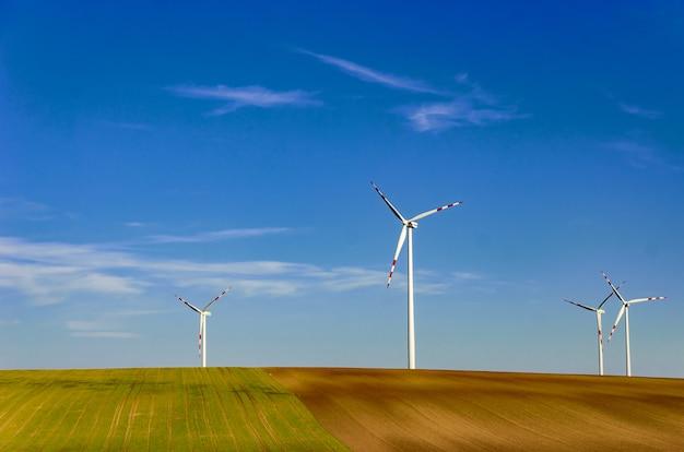 青い空を背景に緑の野原の風車。自然に優しいリソース抽出システム。
