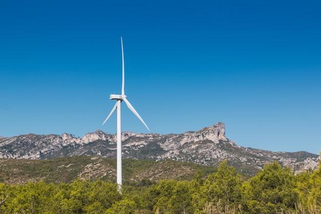 樹木が茂った山の上に風車