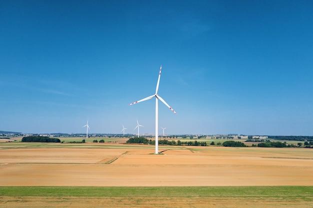 Windmill turbine in the field at summer day rotating wind generator