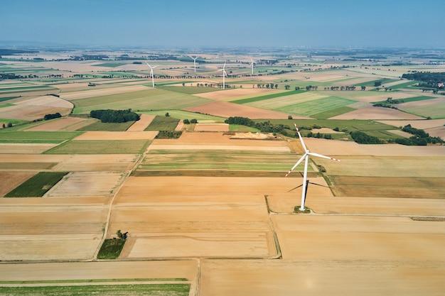 Ветряная мельница в поле в летний день, вращающийся ветрогенератор