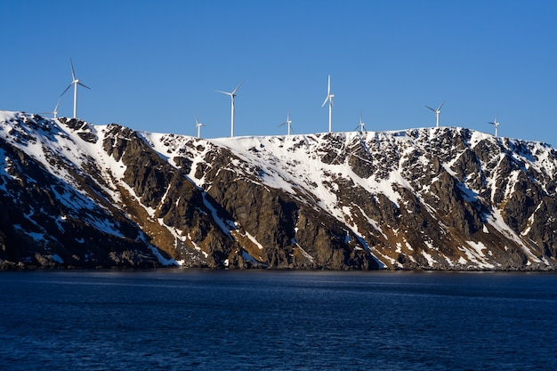 Windmills are installed along the ocean. wind energy in norway.