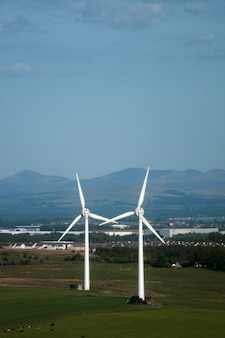 Windmills in the field on the background of villige and mountains west lothian scotland uk