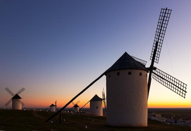 Windmills at field in dusk