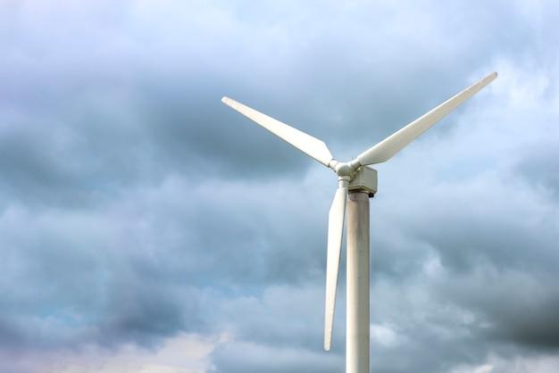 발전용 풍차. 어두운 우울한 하늘, 바람이 부는 날씨, 텍스트를 삽입할 장소를 배경으로 풍력 터빈.