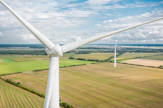 풍차는 들판에서 전기를 생산합니다. 에너지의 대체 소스, 풍력 터빈 높이에서 클로즈업. 드론에서 바라보는 멋진 풍경