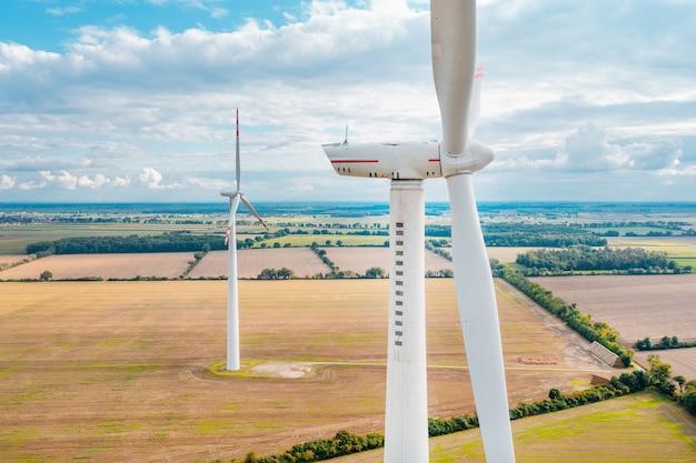 Ветряные мельницы вырабатывают электричество на полях. альтернативные источники энергии, ветряные турбины крупным планом с высоты. красивый вид с дрона