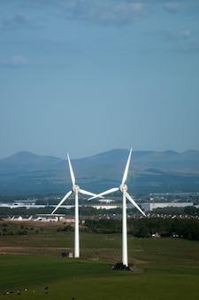 村と山々を背景にした野原の風車ウェストロージアンスコットランド英国