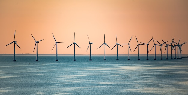 Windmills offshore with sunset