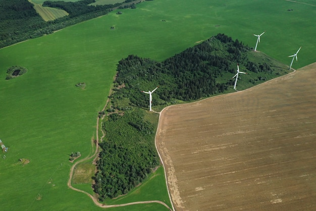 Windmills in summer in a green field.large windmills standing in a field near the forest