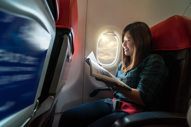 アジアの若い女性は、windoの横に飛行機の中を旅行中に雑誌を読んで