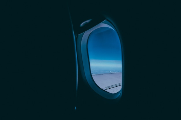 Window of the airplane with the view of the wing and blue sky