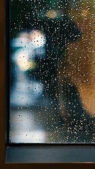Окно и капли дождя в кондоминиуме или квартире в дождливый день в бангкоке, таиланд
