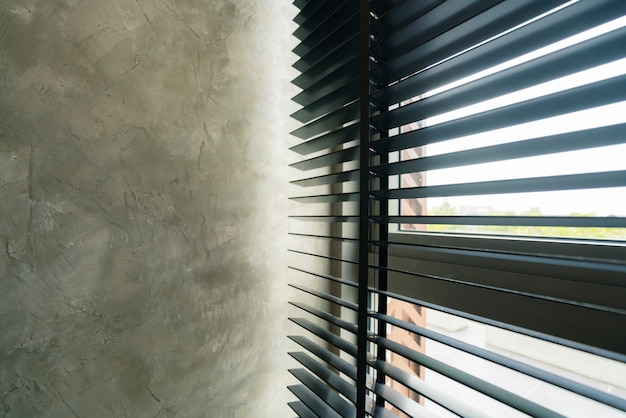Window blind shutter with light shadow and concrete wall