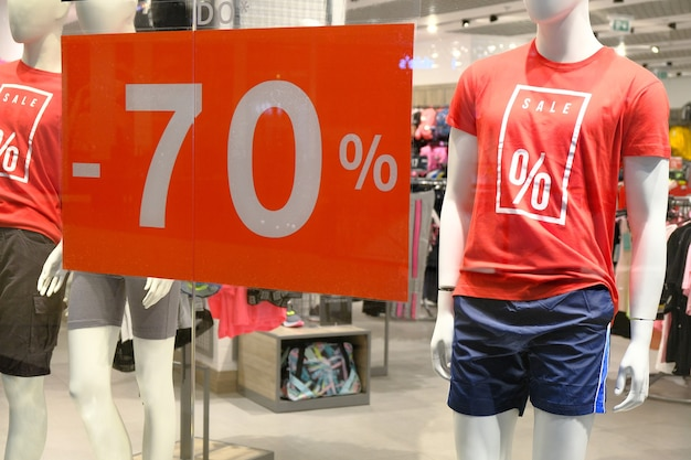 Window of boutique with mannequin in t-shirt with sign advertising sale for sport clothes