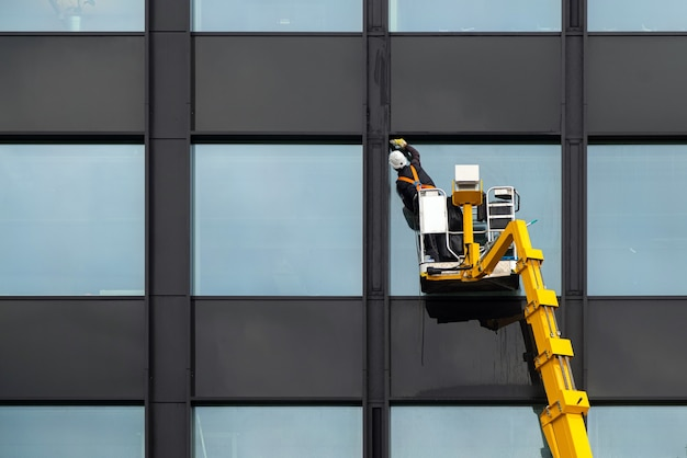 Window cleaner cleaning glass windows on modern building