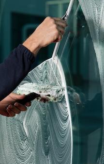 Мойщик окон с помощью ракеля для мытья окон