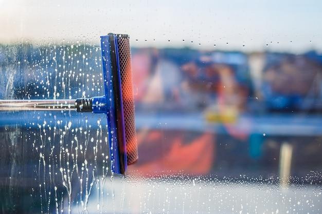 Щетка для мытья окон. большое окно в многоэтажном доме, уборка. мытье окон в многоэтажках, домах щеткой. удаление пыли и мойка стекла.